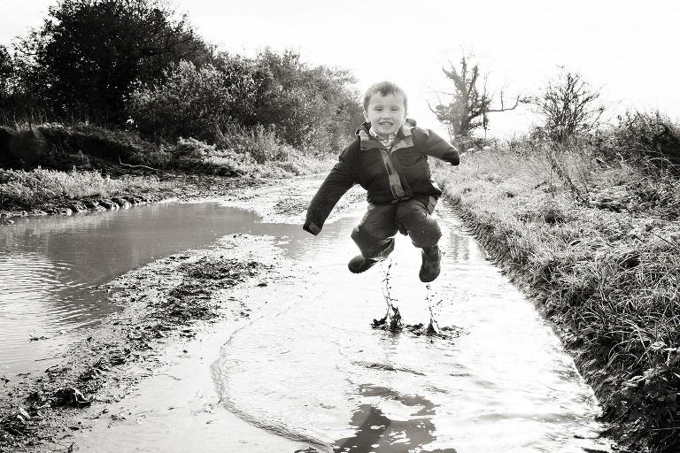 A very happy boy jumping in a puddle